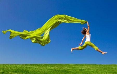 Frau mit Energie springt mit einem grünen Tuch über einen Rasen Blauer Himmel