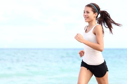 Frau joggt am Meer und ist glücklich Sport