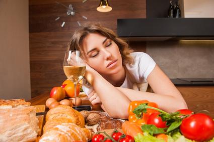 Frau schläft am Tisch Glas mit Wein Gemüse Blutzuckerregulierung