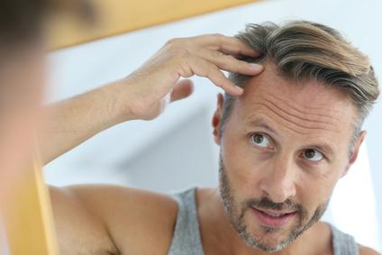 Mann bemerkt seinen Haarausfall