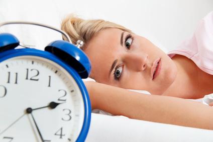 Frau mit Schlafstörungen blickt auf blauen Wecker